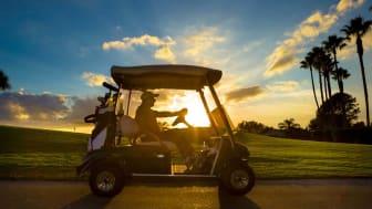 A senior man drives his golf cart at a Florida resort
