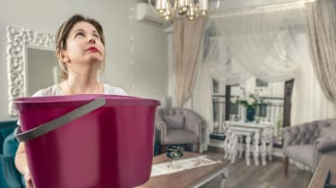 A woman holds a bucket up in her dining room to catch drips from a leaky roof.