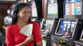 picture of woman in casino hold several one-hundred dollar bills
