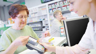 Senior citizen paying for prescription at a pharmacy using a credit card