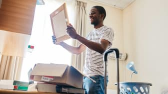 Student in dorm room holds up a frame just removed from a package