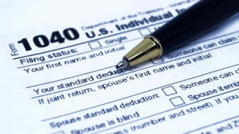 picture of a 1040 tax form with a pen laying on it next to the standard deduction line