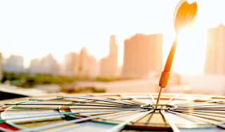 Red dart arrow hitting in the target center of dartboard with modern city and sunset background. Target business, achieve and victory concept . (Red dart arrow hitting in the target center of