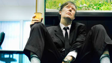 A disheveled man in a suit sits on the floor.