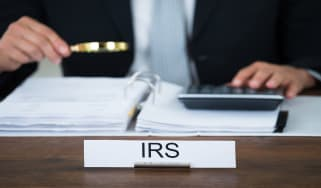 picture of IRS auditor looking at a tax return with a magnifying glass