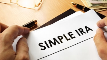 A person sitting in front of a document that says SIMPLE IRA