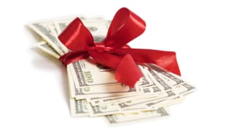A stack of money wrapped with a red ribbon