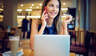 Young girl is sitting in a cafe, and shopping online using her credit card