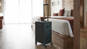 Suitcase by bed in hotel room at tourist resort