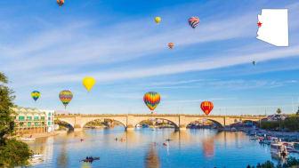 Hot air balloons rise over a river in downtown Lake Havasu City, Ariz.