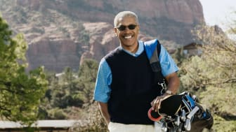 Golfer on a course in Arizona with mountains behind him
