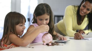 Two sisters inserting coins into a piggy bank with their mother smiling near them
