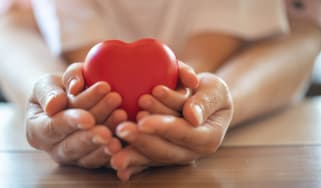 Adult and child holding heart symbolizing charity