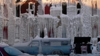 Ice-covered vehicles and building.