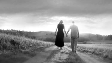A couple walks hand-in-hand down a country road.