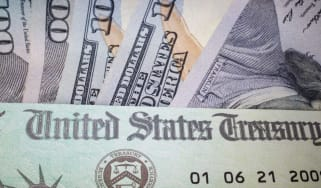 Photo of stimulus check in front of U.S. currency