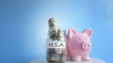 Concept art of a piggy bank with HSA written on it next to a jar of money