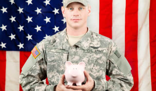 A soldier holds a piggy bank.