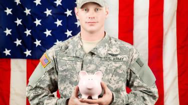 A soldier holds a piggy bank.