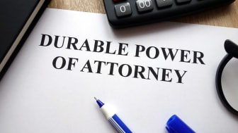 Durable power of attorney document, pen, glasses and calculator on desk