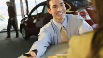 Car salesman smiling at customer
