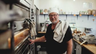 Photo of man at pizza oven