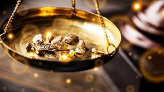 Gold nuggets in a weight pan