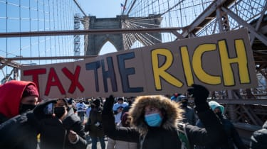 """picture of protester on bridge holding large sign saying """"Tax the Rich"""""""