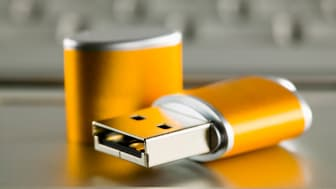 Open thumb drive next to a computer laptop