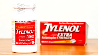 A bottle of Tylenol sitting next to a box of Tylenol