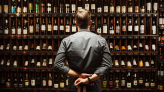 A wine sommelier at a restaurant looks at a wall full of bottles.