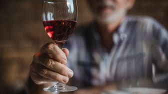 Senior toasting with a glass of red wine