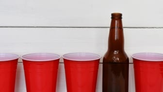 4 red Solo cups and a bottle of beer