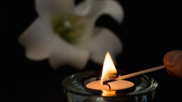 Hand lighting tea light candle with white lily in background