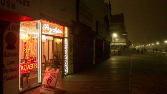 Fog-shrouded New Jersey boardwalk with palm reader store open