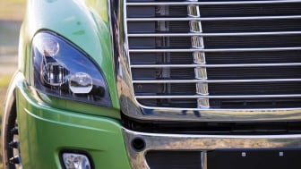 Sunlit stylish and comfortable green big rig semi truck of latest model of commercial long-distance transport with shiny chrome grille and efficient headlight in the parking lot waiting for c