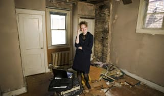A landlord stands in a run-down house.