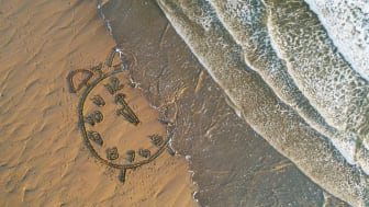 A drawing of a clock in the sand of a beach is washed away by waves.