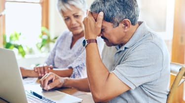 A couple looks at a computer while seeming stressed.