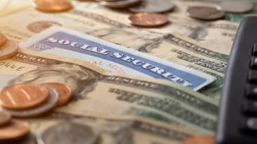 A social security card sits atop some cash