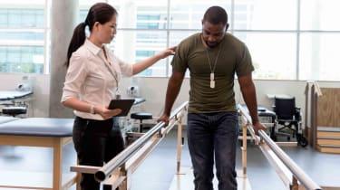 Guy walking between balancing poles, doctor steadies him