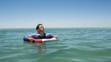 Businessman floats with a life preserver around him.