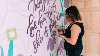 A muralist paints a slogan on a bedroom wall