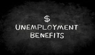 "picture of a dollar sign and the words ""unemployment benefits"" written on a black board"
