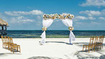 Fresh flower arbor on the beach with eight chairs for a small beach wedding with a view of the Caribbean Sea.