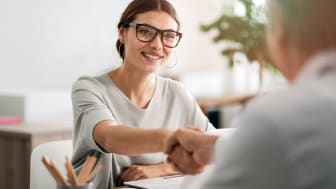 picture of woman professional shaking hands with a client while sitting at her desk