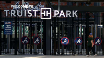 ATLANTA, GEORGIA - MARCH 26:A patron looks through the locked gates of Truist Park, home of the Atlanta Braves, on March 26, 2020 in Atlanta, Georgia.Major League Baseball has postponed the s
