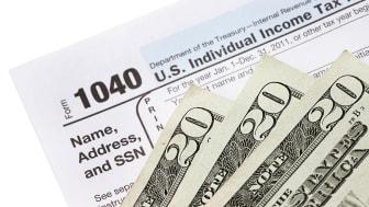 picture of three twenty-dollar bills laying on a tax form