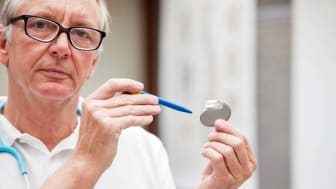 A mature doctor, pointing at a cardial pacemaker. XXXL size image. Image taken with Canon EOS 5 Ds and EF 70-200mm 2,8 USM L.