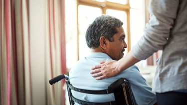A man in a wheelchair gets a pat on the back from a caregiver.